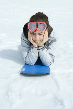 Preteen girl lying on snowboard in snow, portrait