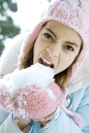 Preteen girl eating snow out of mittened hands, snarling and looking at camera