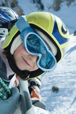 kids at the ski lift: Girl wearing ski goggles and helmet, smiling at camera, portrait