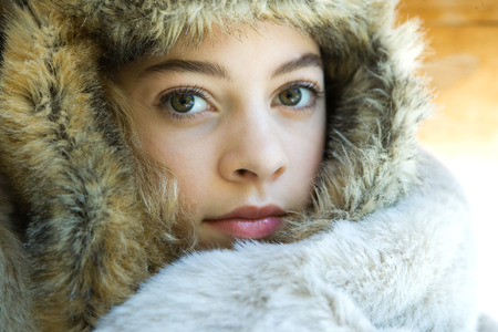 furs: Preteen girl, wearing fur hat, wrapped in fur blanket, looking at camera, close-up portrait