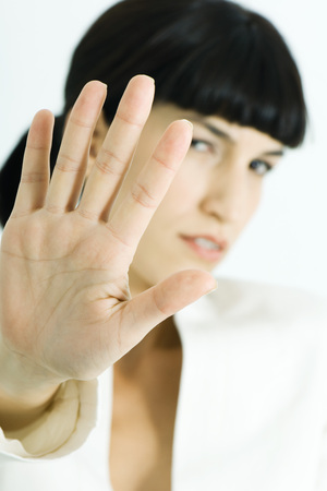 Woman holding up palm to camera, portrait