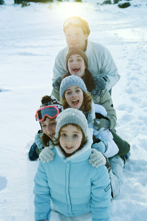 Group kneeling in snow, lined up one behind the other, smiling and laughing LANG_EVOIMAGES