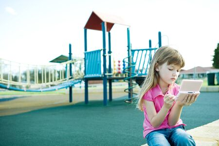Child on playground, playing video game