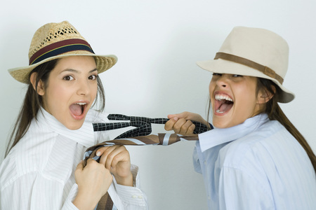 Two young female friends dressed in hats, pulling each others ties, laughing at camera LANG_EVOIMAGES
