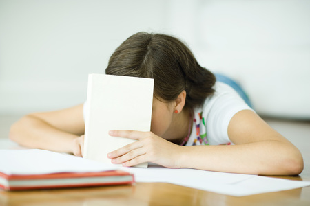 Teen girl lying on floor, doing homework, holding book in front of face