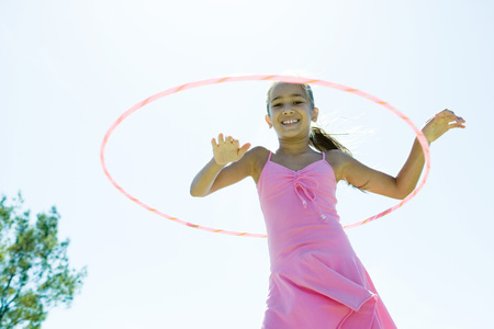 Girl playing with plastic hoop