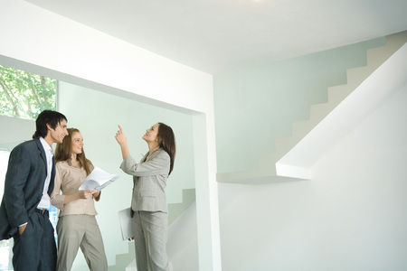Female real estate agent showing house to young couple, pointing to ceiling