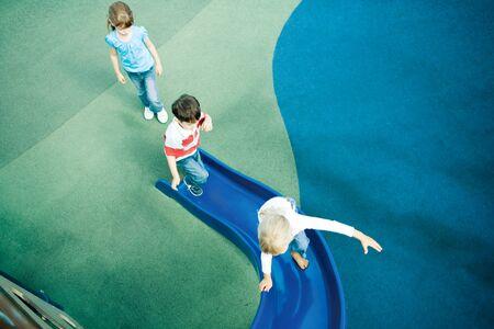 pasto sintetico: Children on playground equipment