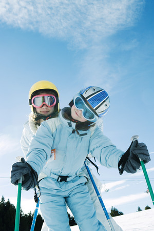 kids at the ski lift: Two young skiers standing, one behind the other, both smiling at camera, low angle view