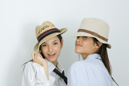 Two young female friends wearing hats and ties, smiling at camera, one looking over shoulder