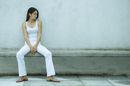 Woman sitting on bench, looking at empty place next to her