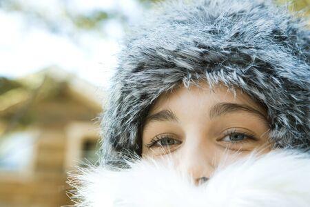 Teenage girl wearing fur hat and fur collar, close-up portrait