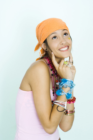 Teen girl wearing lots of accessories, fingers at sides of cheeks, looking up