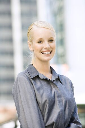 Young businesswoman smiling at camera, waist up, portrait LANG_EVOIMAGES