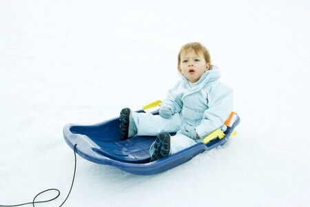 puzzlement: Little boy sitting on sled, looking up, furrowing brow