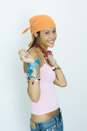 Teen girl wearing lots of accessories, hands up, smiling at camera, portrait