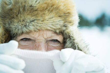 furs: Senior woman pulling up turtleneck over face, close-up, portrait LANG_EVOIMAGES