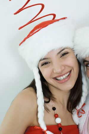 Two young female friends dressed in Christmas costumes, smiling at camera, portrait, cropped LANG_EVOIMAGES