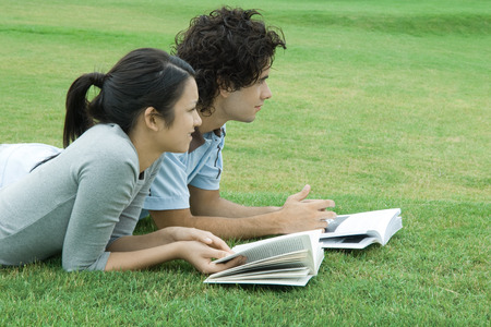 distractions: Young couple lying on grass with books, looking out of frame