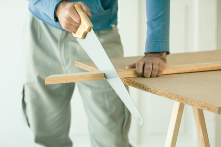Man sawing piece of wood, cropped view