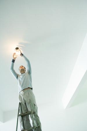 Man changing light bulb LANG_EVOIMAGES