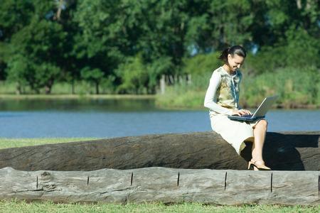 Woman sitting on tree trunk, using laptop