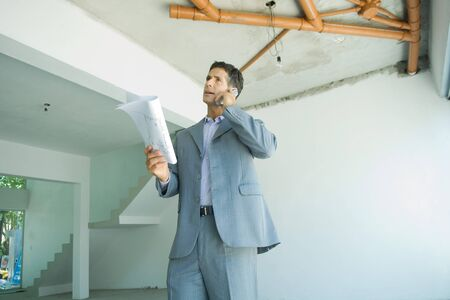 Well-dressed man holding blueprints, using phone, inspecting unfinished home interior LANG_EVOIMAGES