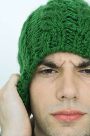 Young man wearing knit hat, furrowing brow, portrait, close-up