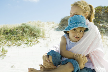 leaning against: Little boy with mother on beach LANG_EVOIMAGES