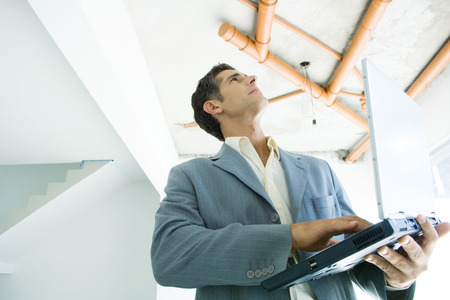 Well-dressed man using laptop, inspecting unfinished home interior LANG_EVOIMAGES