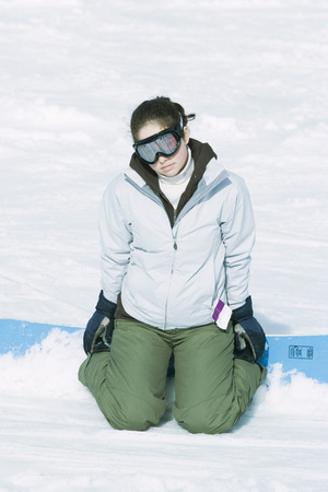 Teenage girl kneeling in snow with snowboard, looking at camera LANG_EVOIMAGES