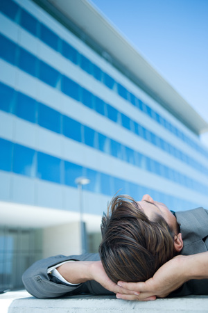 Businessman lying on ground outdoors, hands behind head, cropped view