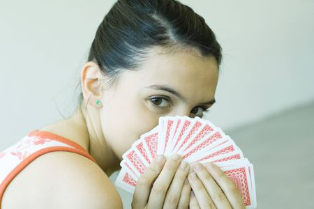 Teen girl looking over hand of cards
