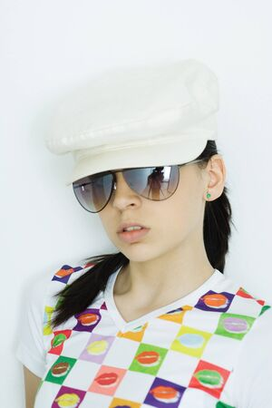 Teen girl wearing cap and sunglasses, portrait