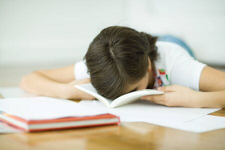Teen girl lying on floor, doing homework, resting face in book
