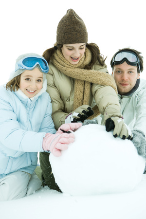 Three young friends crouching in snow, making large snowball together, two smiling at camera