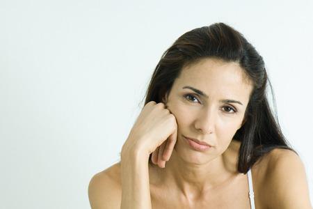 Woman holding head, pouting, portrait