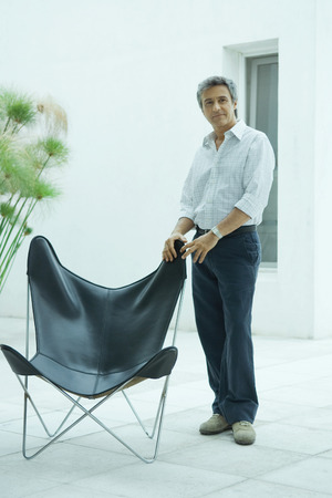 open windows: Mature man standing by chair, full length portrait