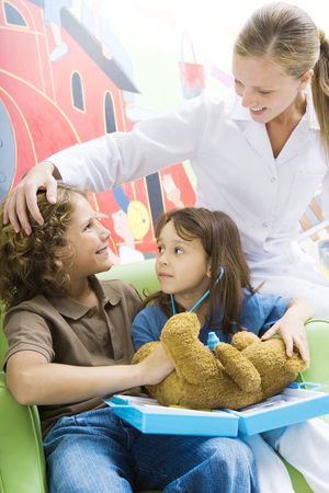 Boy and girl playing doctor with teddy bear while nurse watches LANG_EVOIMAGES