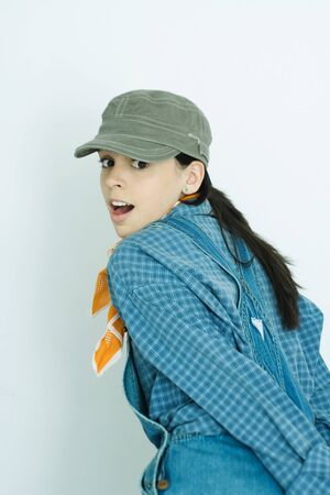 Teen girl wearing overalls and cap, looking over shoulder at camera LANG_EVOIMAGES