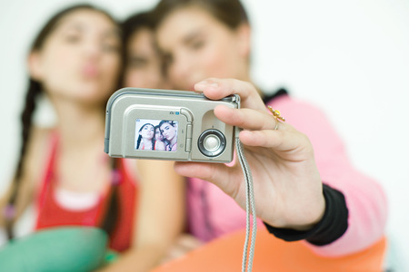 Three young female friends taking photo of selves with digital camera, focus on camera in foreground