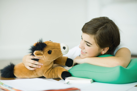 attachment: Teen girl lying on floor, smiling at stuffed toy horse LANG_EVOIMAGES