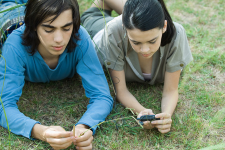 Teen couple listening to MP3 player together, lying on grass