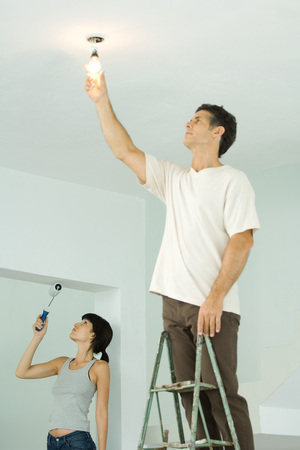 Woman painting with paint roller, man changing light bulb