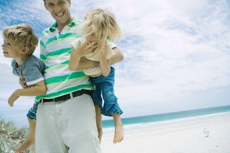 Man holding children under his arms on beach