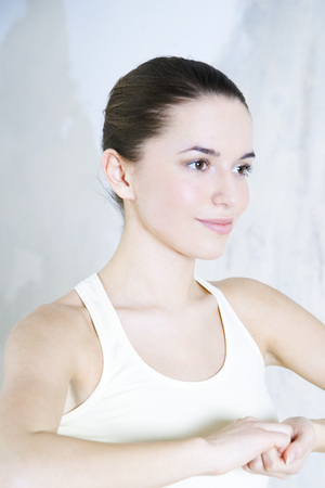 Young woman doing yoga pose, clasped hands, smiling, head and shoulders