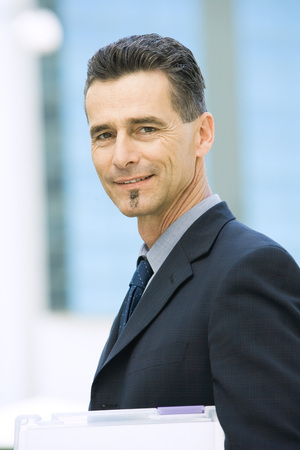 Mature businessman smiling at camera, head and shoulders, portrait