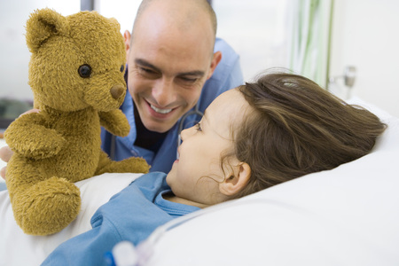 Girl lying in hospital bed, nurse holding up teddy bear LANG_EVOIMAGES