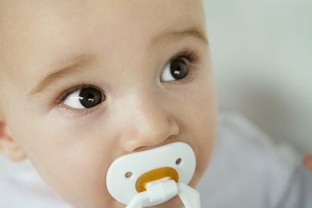 Baby with pacifier in mouth, raising eyebrows, close-up LANG_EVOIMAGES