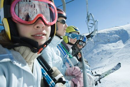 kids at the ski lift: Four young skiers on chair lift, two looking at camera